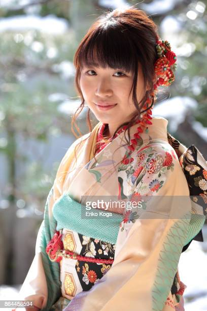Young woman of coming‐of‐age ceremony sitting on chair in front of snowy Japanese garden