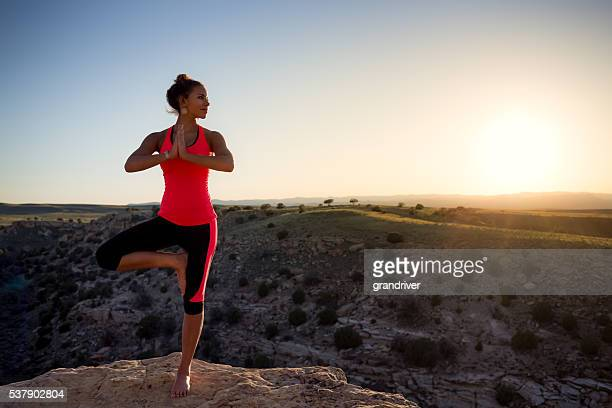 Young Woman Of Ethnic Descent Performing Yoga Outdoors