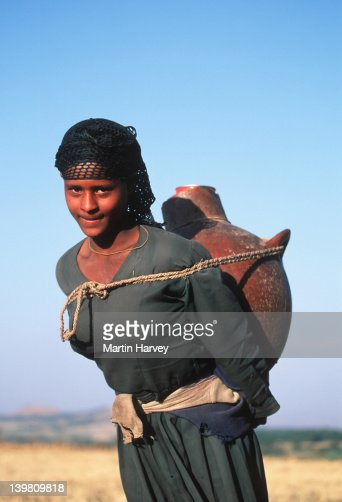 Young woman of the Amhara tribe carrying water container, Ethiopia.