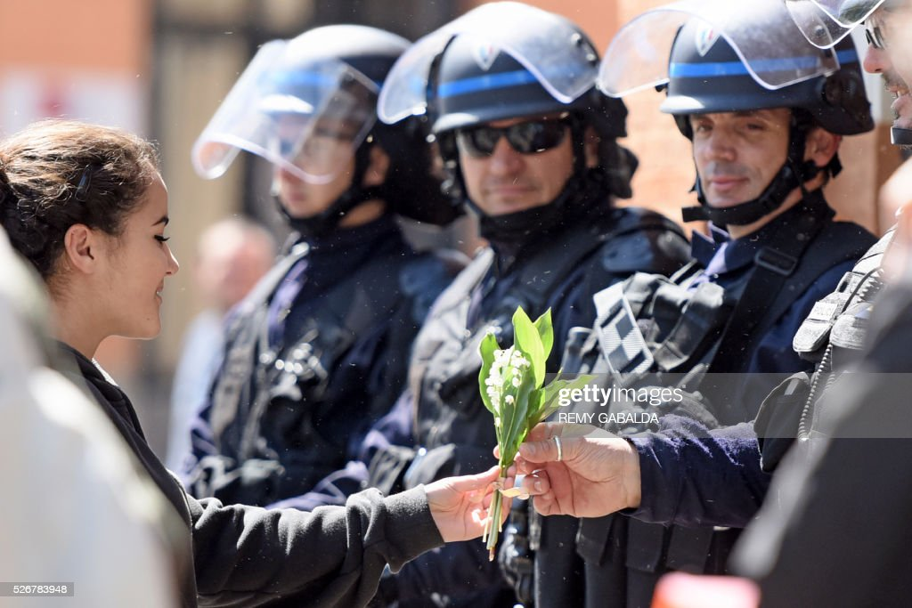 A young woman offers a bouquet of lily of the valley to a police officer during the traditional May Day demonstration in Toulouse, southern France, on May 1, 2016. / AFP / REMY