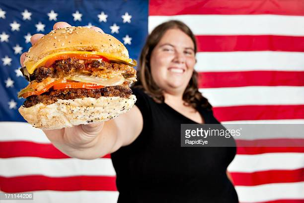 Young woman offers cheeseburger in front of US flag