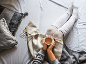 young woman sitting on a bad holding a cup of hot coffee on a cold winter morning at home