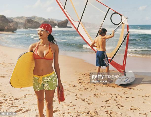 Young Woman on a Beach Holding a Surf Board and Flip Flops and Man Behind Preparing His Windsurf Board