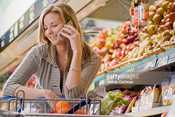 Young Woman on a Cellphone at the Supermarket