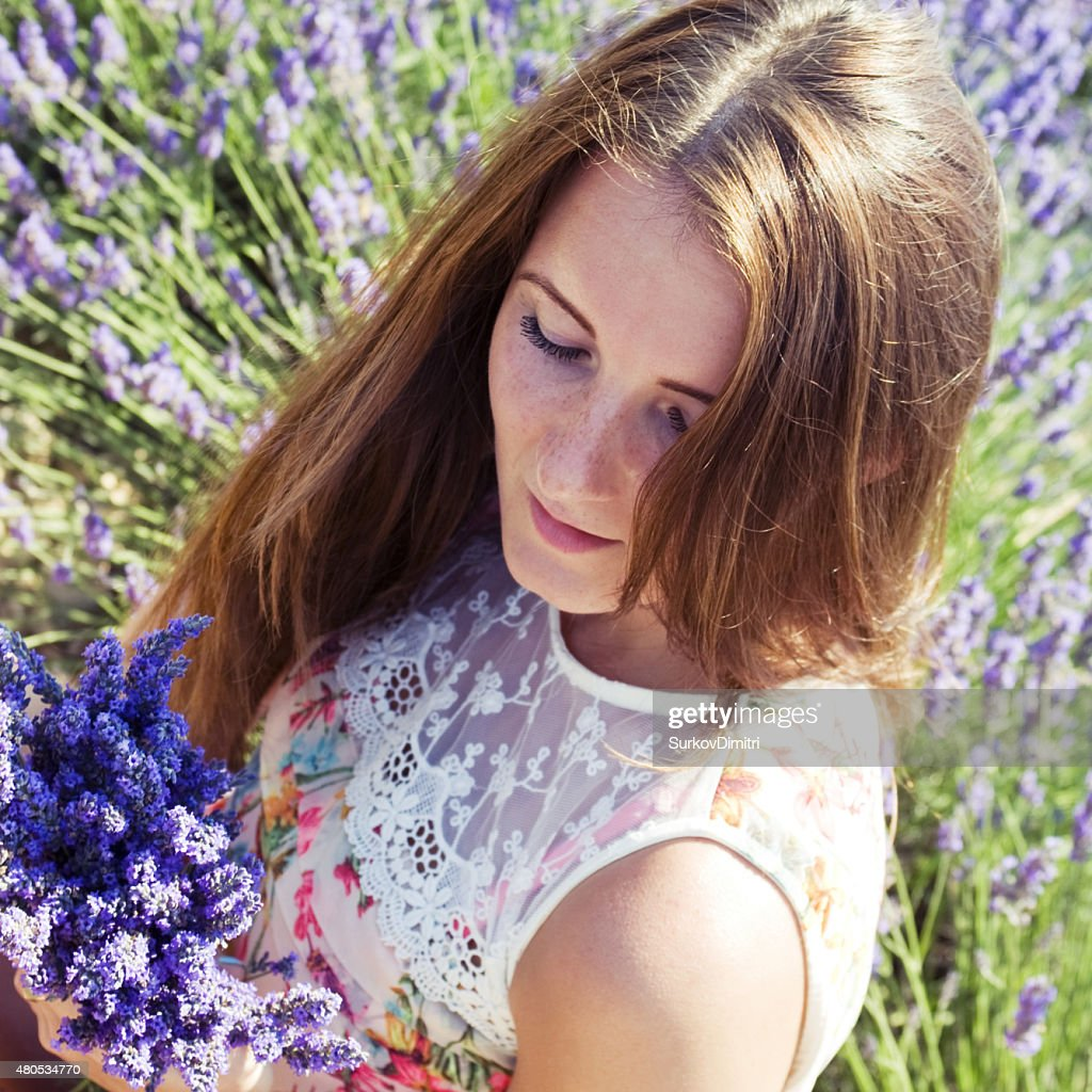 Young woman on a meadow with lavender flowers : Stockfoto