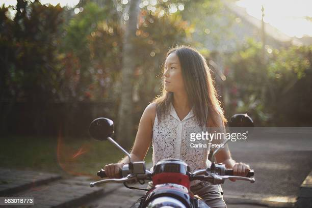 A young woman on a motorbike in Bali