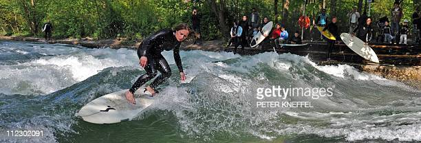 A young woman on a surfboard rides on the waves of the Eisbach creek at the Englischer Garten park in Munich southern Germany on April 18 2011 Spring...
