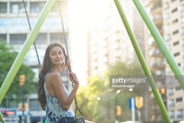Young woman on a swing in the city