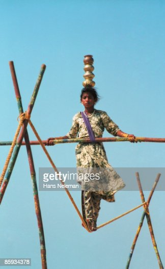 Young woman on a tightrope balancing jars. : Stock Photo
