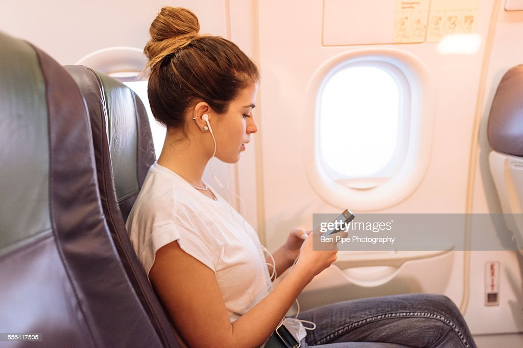 Young woman on airplane choosing music on smartphone : Stock Photo