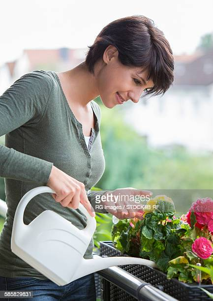 Young woman on balcony watering flowers