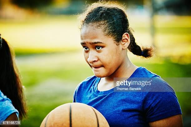 Young woman on basketball court on summer evening