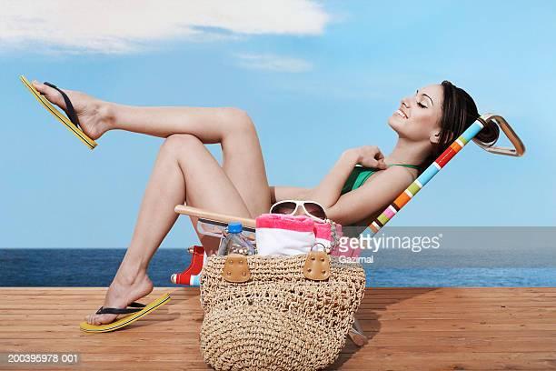 Young woman on beach chair sunbathing on beach deck