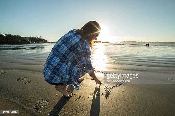 Jeune femme sur la plage de dessin de coeur sur la plage au coucher du soleil