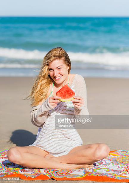 Young woman on beach eating watermelon, Jupiter, Florida, USA