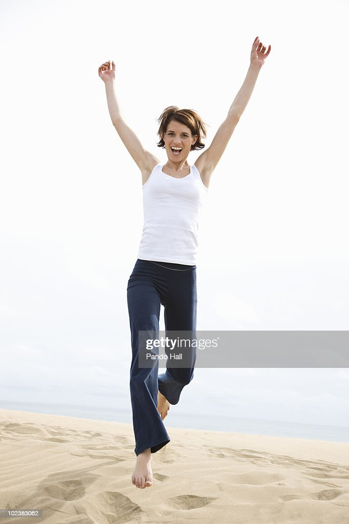 Young woman on beach jumping, laughing : Stock Photo