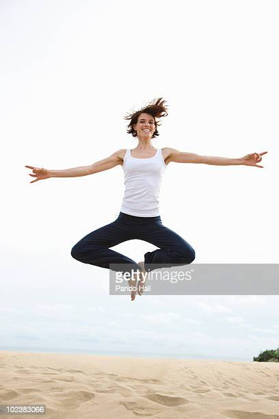 Young woman on beach jumping, laughing