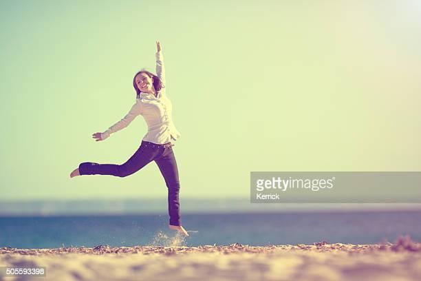Jovem mulher na praia com os braços para cima Salto