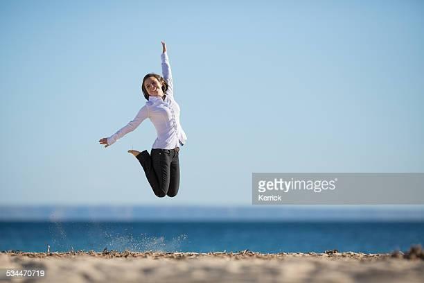 若い女性をジャンピングまで、腕のビーチ