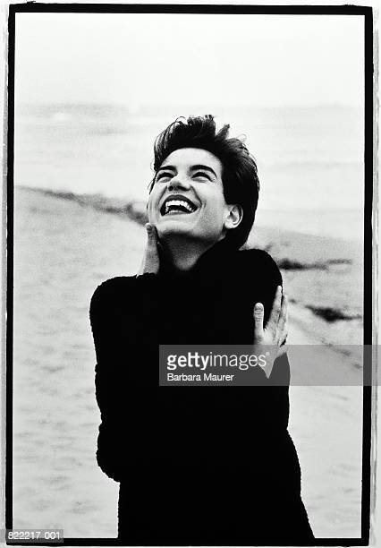 Young woman on beach, laughing (B&W)