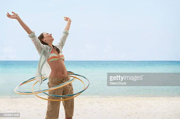 Young woman on beach playing with hula hoops