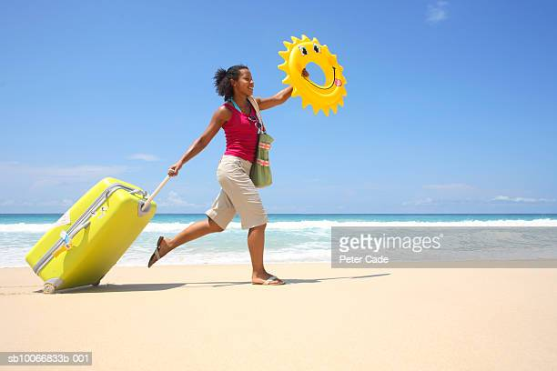 Young woman on beach pulling suitcase and holding rubber ring, side view