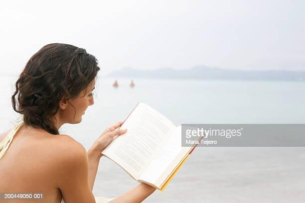 Jeune femme sur la plage, livre, vue de dos