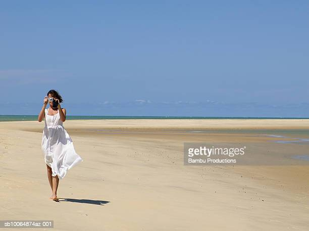 Young woman on beach taking photograph