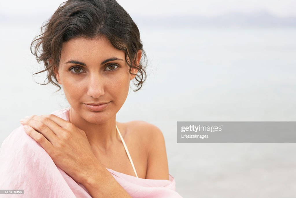 Young woman on beach, wearing pink stole, close-up, portrait : Stock Photo
