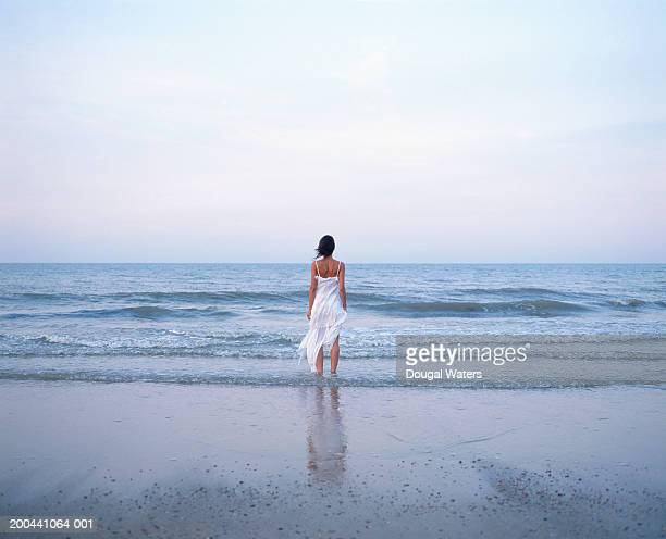 Young woman on beach wearing white dress, facing ocean, rear view