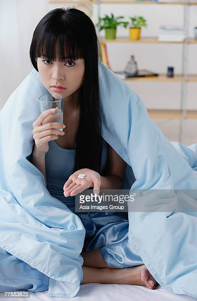 Young woman on bed, holding glass of water and pills