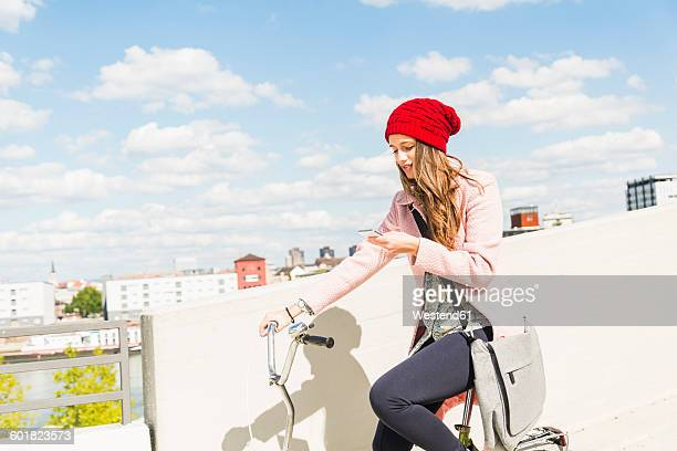 Young woman on bicycle looking at cell phone