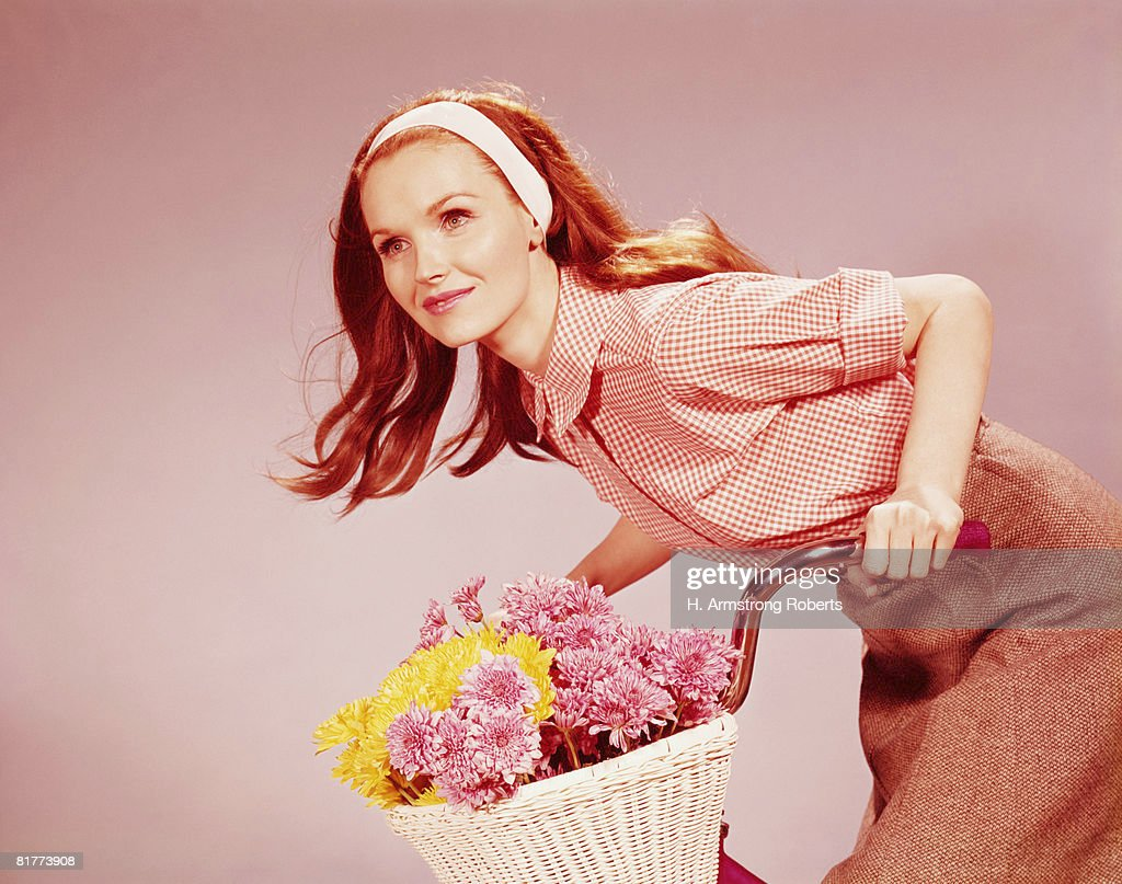 Young woman on bicycle with basket full of chrysanthemum flowers. (Photo by H. Armstrong Roberts/Retrofile/Getty Images) : Stock Photo