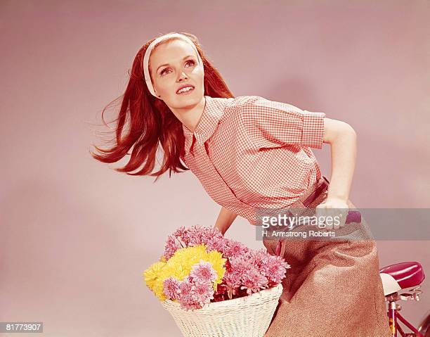 Young woman on bicycle with basket full of flowers. (Photo by H. Armstrong Roberts/Retrofile/Getty Images)