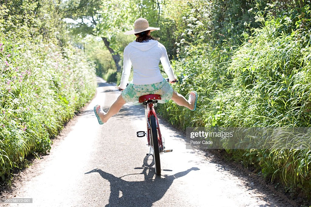 Young woman on bicycle with legs spread open, rear view : Stock Photo
