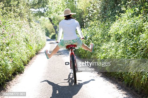 Young woman on bicycle with legs spread open, rear view : Foto stock