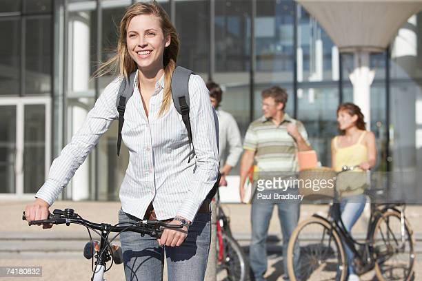 Giovane donna in bicicletta con studenti in background
