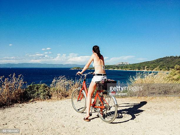Young woman on bike looking to the sea