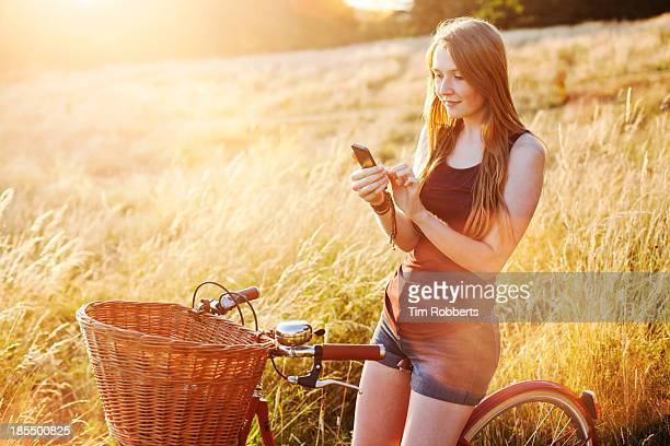 Young woman on bike using smart phone in field