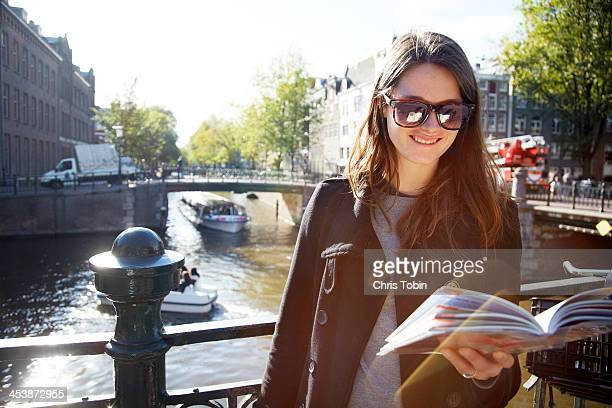 Young woman on bridge with guidebook