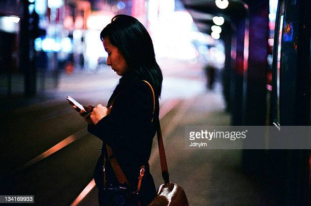 Young woman on bustop at night
