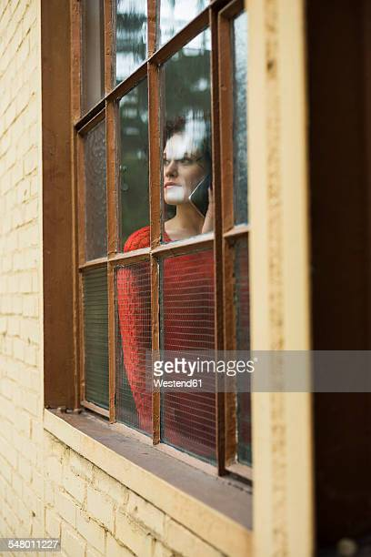 Young woman on cell phone behind window
