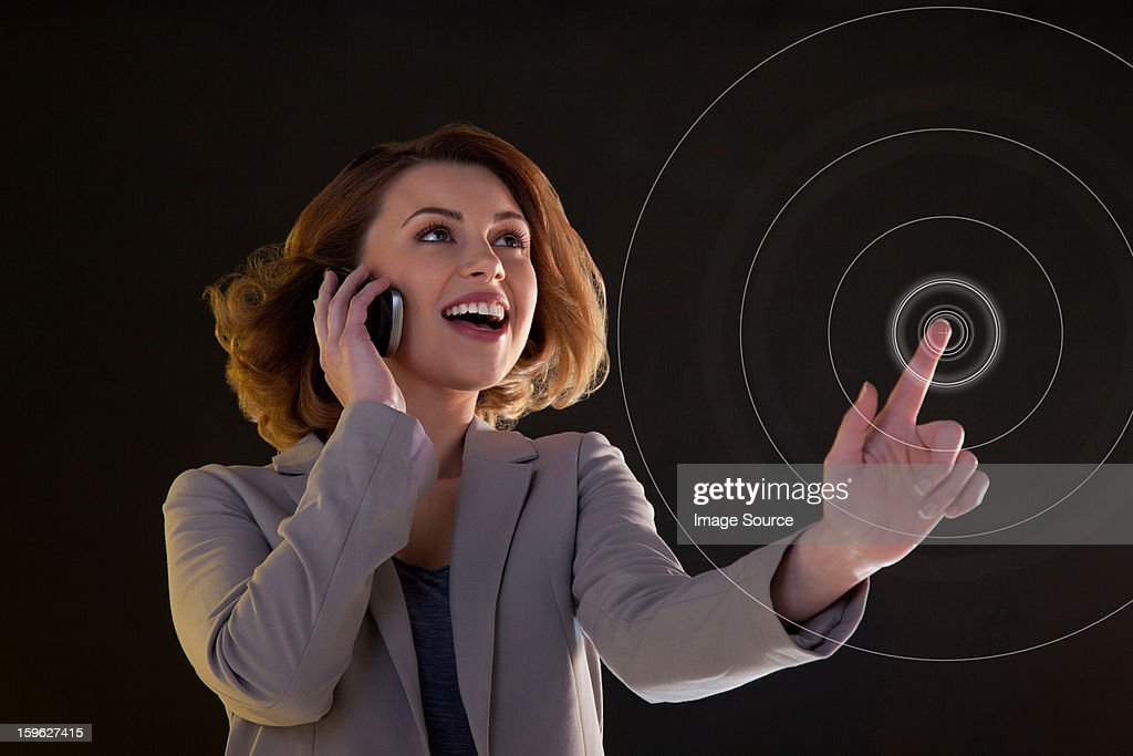Young woman on cellphone and touching virtual circle : Stock Photo