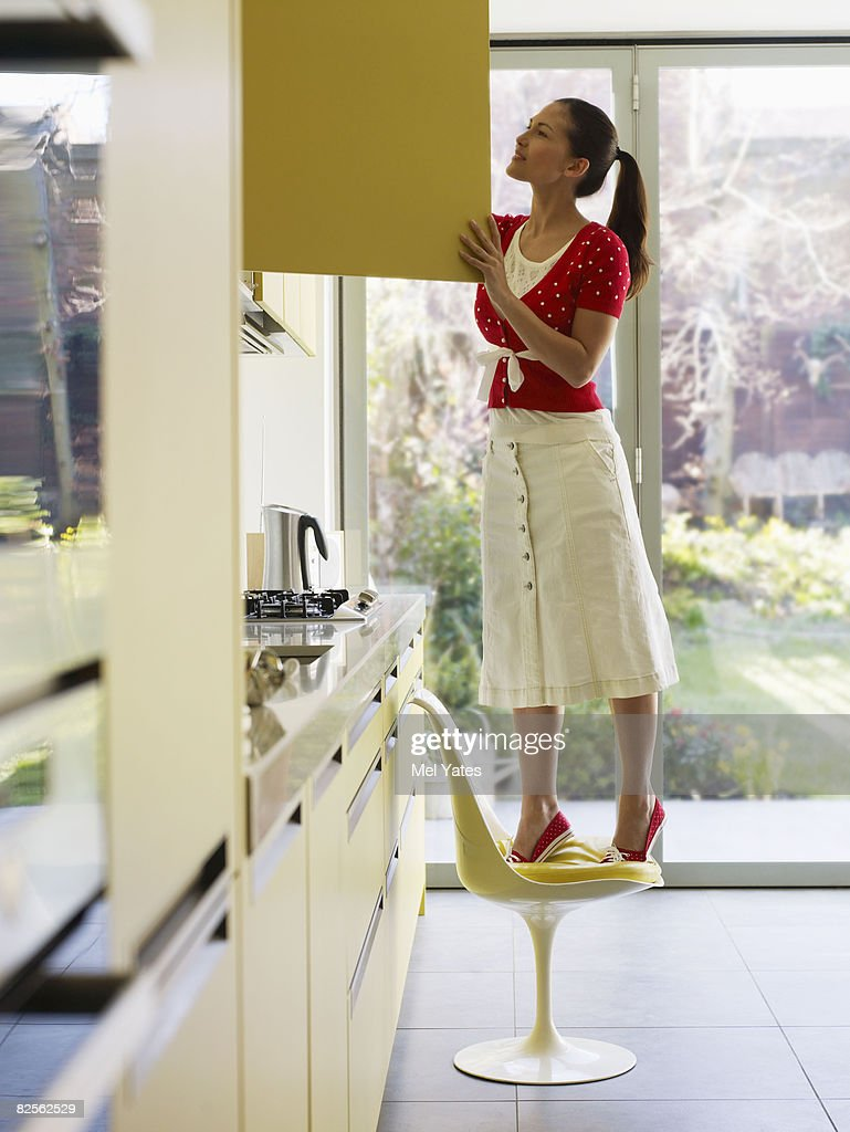 Young woman on chair looking in cupboard
