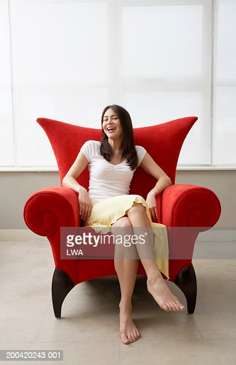 Young woman on chair, smiling, portrait