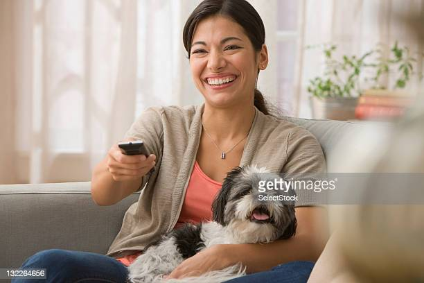 Young woman on couch with dog and remote control