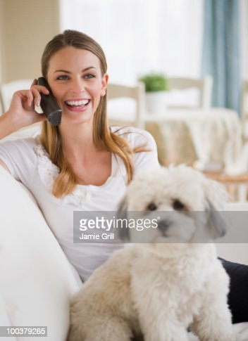 Young woman on couch with dog, talking on phone : Foto de stock