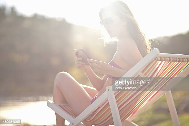 Young woman on deckchair texting from cellphone