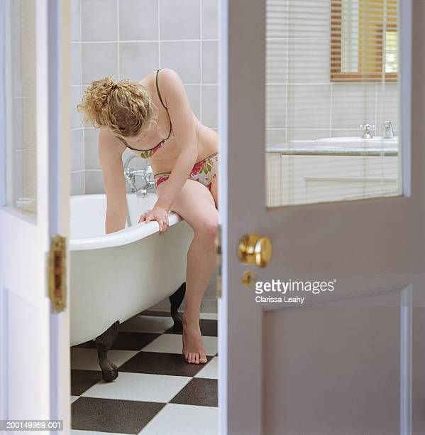 Young woman on edge of bath, hand in tub, view through doorway