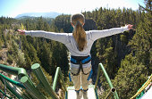 Young woman on edge of bungee platform, rear view, (wide angle)